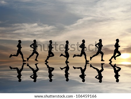 Silhouette of runner with reflection during a surreal dramatic sunset. - stock photo