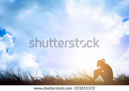 Silhouette of sad a woman depressed sitting alone on meadow. - stock photo