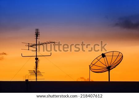 Silhouette of satellite dish and telecommunication pole  - stock photo