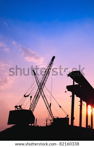 Silhouette of several cranes working at sunset in a harbor - stock photo