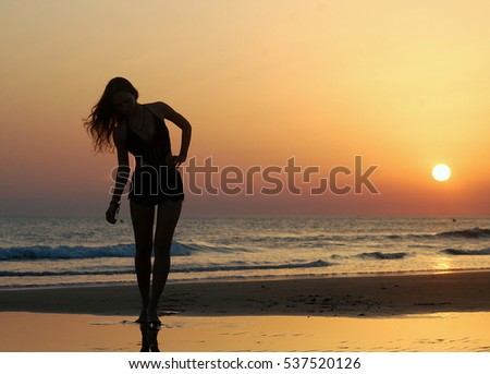 Silhouette of sexy woman over sunset