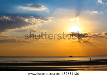 Silhouette of ship floats in the sea on a spectacular sunset not far from the coast - stock photo