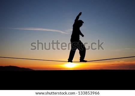 silhouette of slackliner in sunset - stock photo