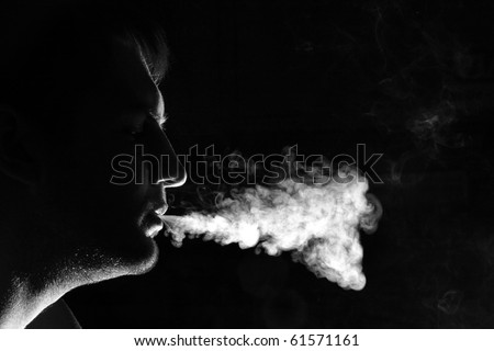 Silhouette of smoker exhales smoke - stock photo