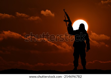Silhouette of soldier or officer with weapon at sunset - stock photo