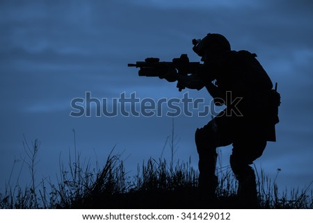 Silhouette of soldier with rifle on a dark blue background