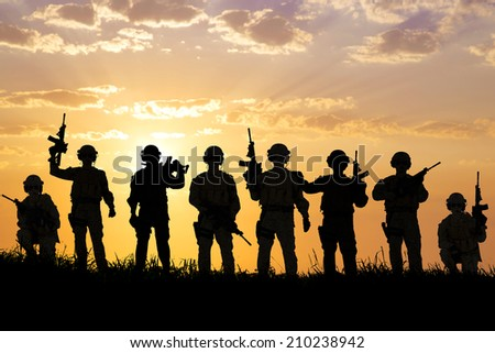 silhouette of  Soldiers team with sunrise background  - stock photo