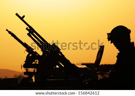 Silhouette of soldiers with a machine gun on the vehicle. - stock photo
