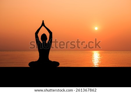 Silhouette of sport slim woman making yoga poses on the beach with Seaview in sunset - stock photo