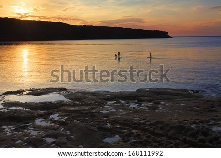 Silhouette of stand up paddle boarders enjoying the calm seas and a beautiful sunrise on Botany Bay, Australia  SUP is a fairly new sport based on the Hawaiin Hoe he'e nalu.  - stock photo