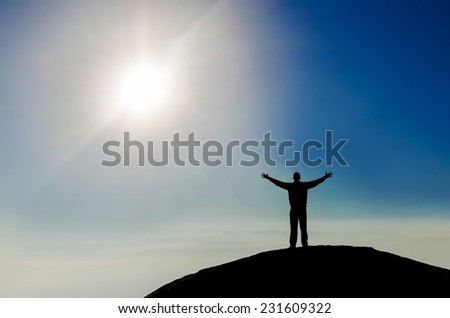 Silhouette of successful businessman and beautiful sky on the top of the world