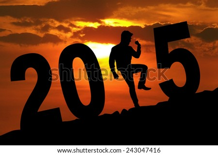 Silhouette of successful businessman celebrate his success while forming number 2015 at sunset time - stock photo