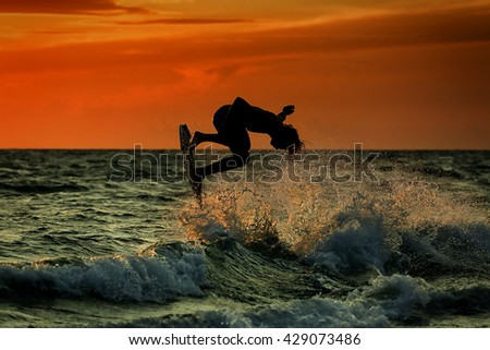 Silhouette of surfer at sunset. Unrecognizable face.