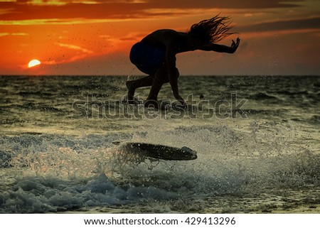 Silhouette of surfer at sunset.  Unrecognizable face.  - stock photo