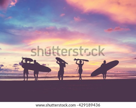 Silhouette Of surfer people carrying their surfboard on sunset beach, vintage filter effect with soft style - stock photo