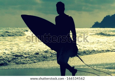 Silhouette of surfer with a board on a sunset evening in Manuel Antonio's National Park main beach, Costa Rica - stock photo