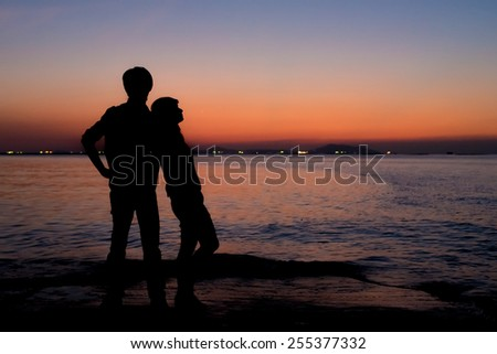 Silhouette of sweet couple with romantic place, Sunset sky at sea - stock photo