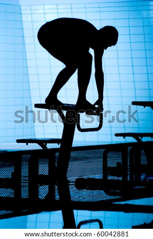 Silhouette of swimmer on starting platform on swimming pool - stock photo
