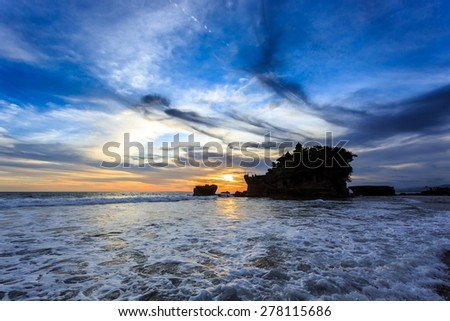 Silhouette of Tahah Lot Temple and ocean waves at sunset, Bali, Indonesia - stock photo