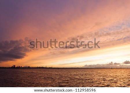 silhouette of tallinn with fire sea sunset - stock photo