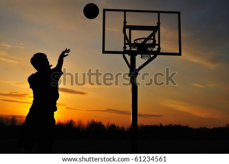 Silhouette of Teen Boy Shooting a Basketball at Sunset - stock photo