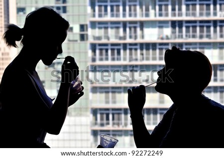 Silhouette of teen sisters having ice cream in hotel room - stock photo