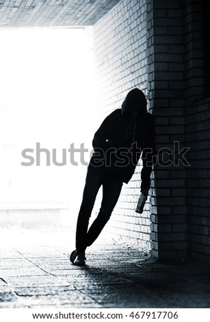 Silhouette of Teenager in the hood holding a beer bottle and standing in the alley