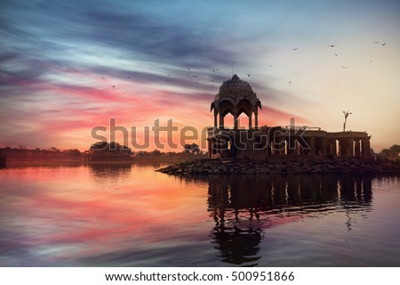 Silhouette of Temple on the Gadi Sagar lake at pink vibrant sunset sky in Jaisalmer, Rajasthan, India
