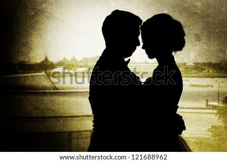 Silhouette of thai couple holding one another facing each other with background of thai temple. Picture was added with vignette and layered old style - stock photo