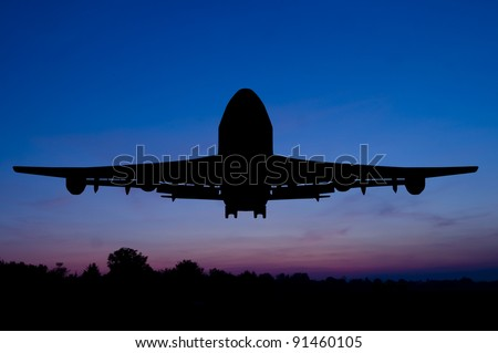 Silhouette of the big plane starting on a sunset background. - stock photo