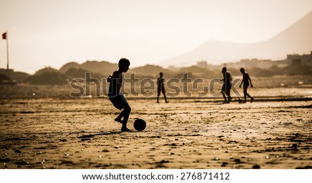 Silhouette of  the boy on the beach with a ball - stock photo