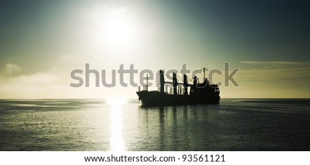 Silhouette of the cargo ship over the sunrise - stock photo
