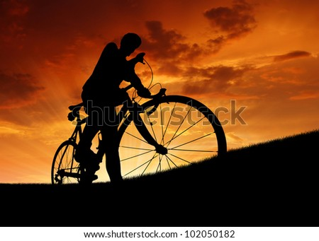 silhouette of the cyclist on road bike at sunset - stock photo