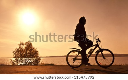 silhouette of the cyclist who rides a bicycle with no hands on r