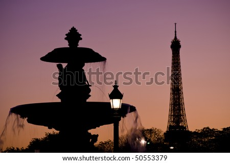 silhouette of the fountain at Place de la Concorde with the Eiffel Tower in the background at dusk - stock photo