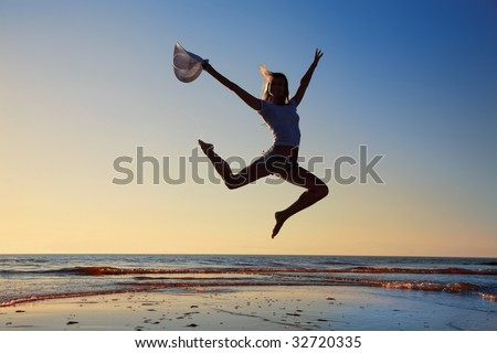 Silhouette of the happy girl jumping on a background of a sunset - stock photo