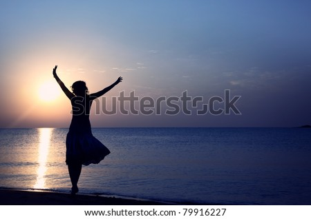Silhouette of the happy woman in summer dress standing at the beach during sunset. Natural light and colors - stock photo