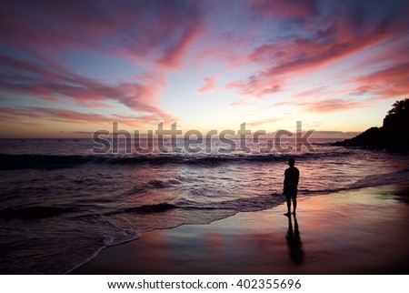 Silhouette of the man standing on the beach at sunset. Colorful skies. Orange horizon. Reflections in the ocean. Spain - Gran Canaria - stock photo