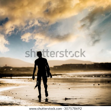 Silhouette of the man walking on the beach with the surfboard at sunset - stock photo