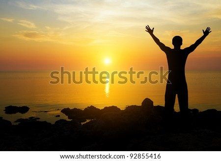 Silhouette of the person on a decline seeing off the sun - stock photo
