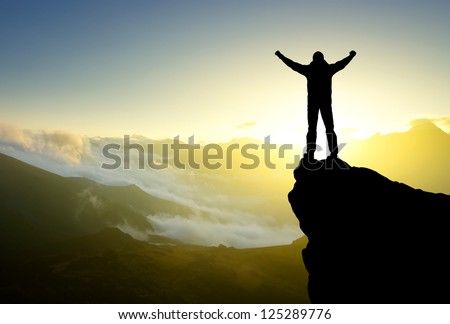 Silhouette of the person on the high rock. Sport and active life - stock photo