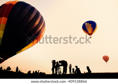 Silhouette of the photographer shoots a photo of hot air balloon - stock photo