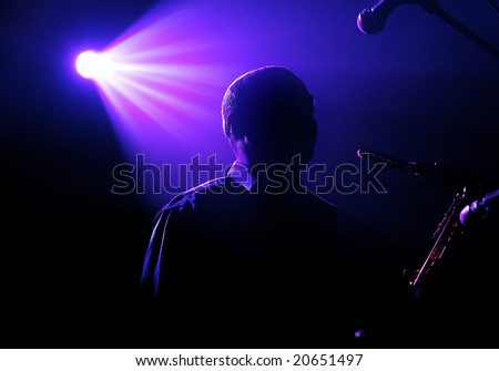 Silhouette of the playing saxophonist under beams of violet light