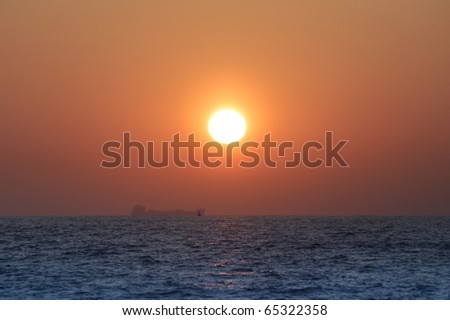 Silhouette of the sea tanker at sunset - stock photo