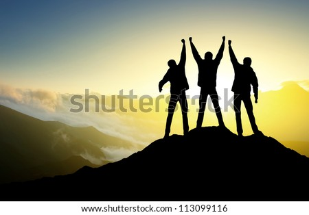 Silhouette of the team on the peak of mountain. Sport and active life - stock photo
