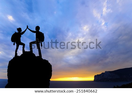 Silhouette of the team on the peak of mountain. Sport and active life of people man and girl - stock photo