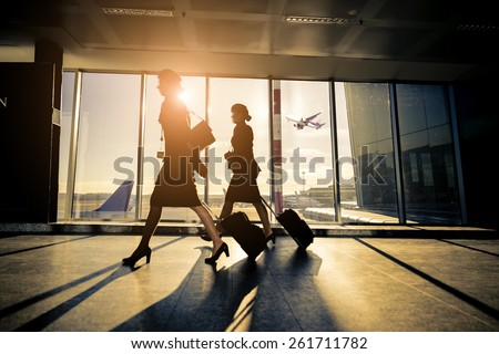 Silhouette of the tourists at airport carrying luggage- Travelers waiting flight at airport - stock photo