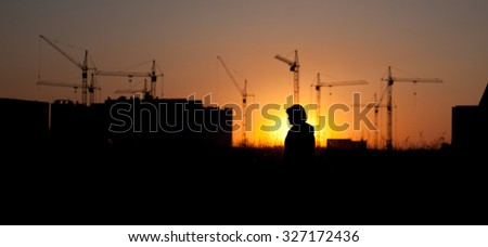 Silhouette of the tower crane on the construction site with city building background - stock photo
