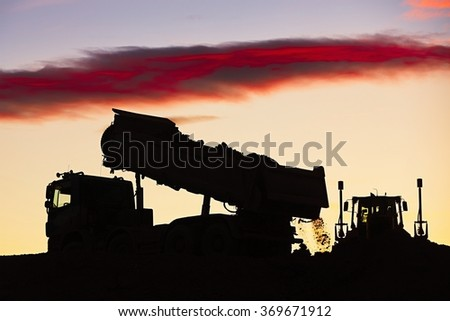 Silhouette of the truck in the building site - stock photo