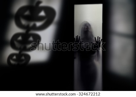 Silhouette of the woman behind the wall with Halloween pumpkin shades - stock photo